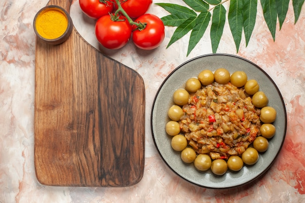 Draufsicht des gerösteten auberginensalats auf teller auf schneidebrett-tomaten auf nackter oberfläche