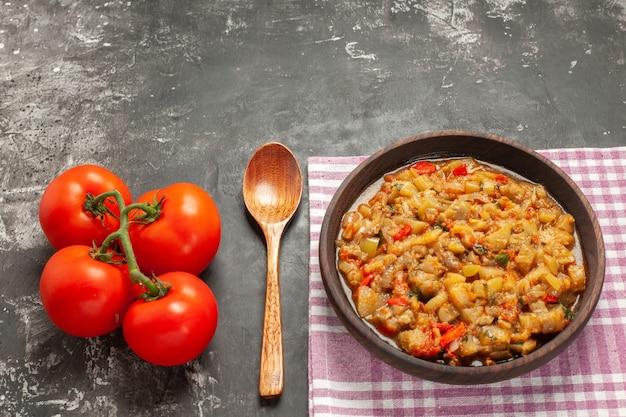 Draufsicht des gerösteten auberginensalats in der schüssel, im holzlöffel und in den tomaten auf dunkler oberfläche