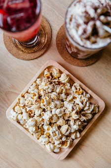 Draufsicht des gesalzenen popcorns diente in der quadratischen hölzernen platte auf holztisch.