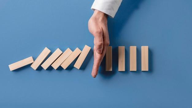 Draufsicht des geschäftsmannes, der dominoeffekt stoppt