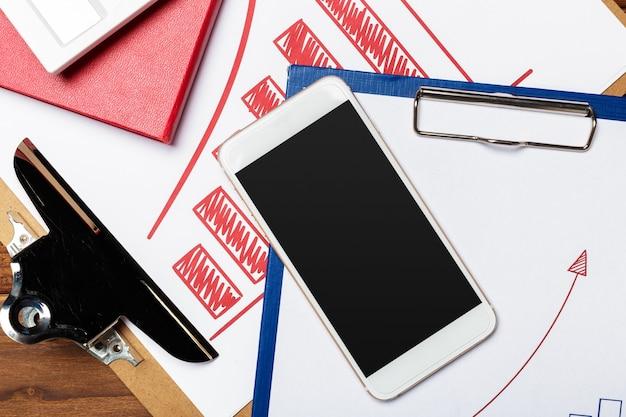 Draufsicht des geschäftspapierdiagramms auf holztisch mit smartphone
