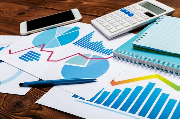 Draufsicht des geschäftspapierdiagramms oder -diagramms auf holztisch