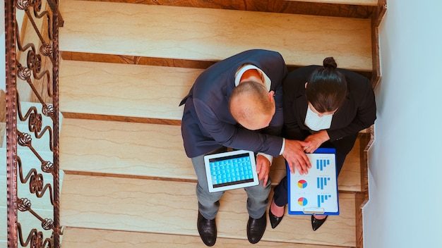 Draufsicht des geschäftsteams, das auf treppen geht und kollegen trifft, die mit tablet arbeiten, frau, die mit dem unternehmensleiter auf der belebten treppe des gebäudes spricht. unternehmer überarbeitung im büro.