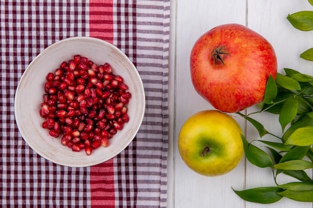 Draufsicht des geschälten granatapfels in einer schüssel mit einem apfel und einem rot karierten handtuch auf einer weißen oberfläche