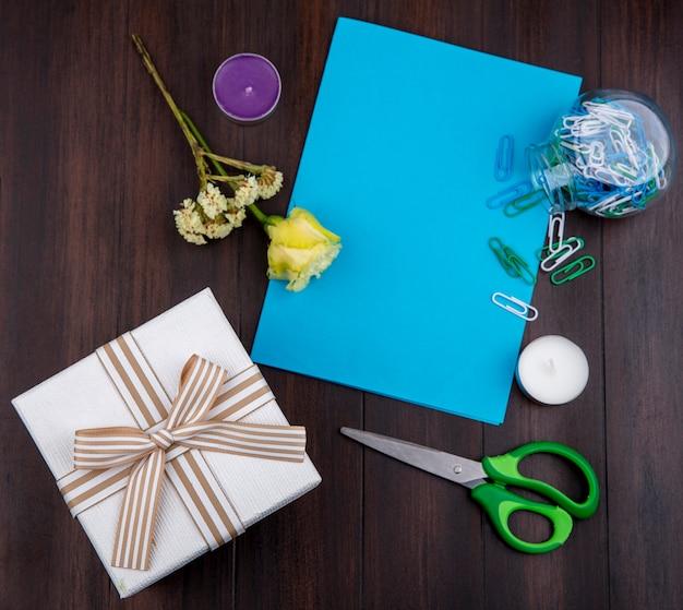 Draufsicht des geschenks mit bogenband mit gelber rose auf einer holzoberfläche mit kopienraum