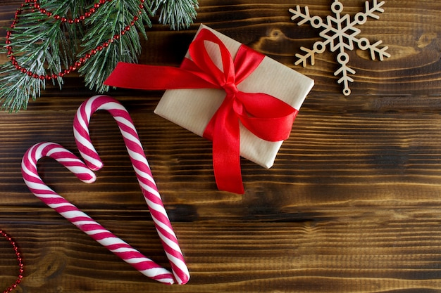Draufsicht des geschenks mit rotem band und weihnachtszusammensetzung auf dem holztisch