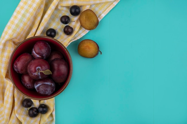 Draufsicht des geschmackskönigs pluots in der schüssel mit traubenbeeren auf kariertem stoff auf blauem hintergrund mit kopienraum