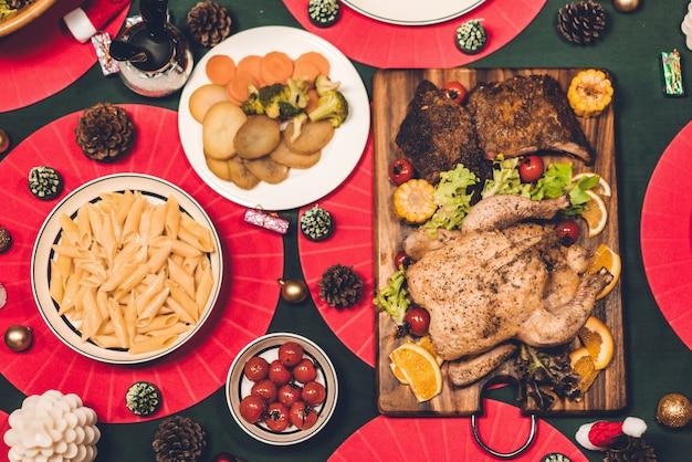 Draufsicht des geschmackvollen gebackenen gebratenen ganzen gebratenen huhns und des salats mit weihnachtsdekoration auf dem weihnachtsthemenorientierten abendtische