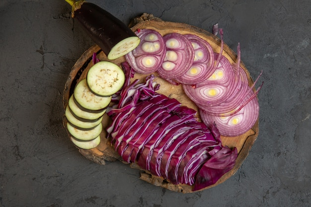 Draufsicht des geschnittenen gemüses roter zwiebelkohl und der aubergine auf einem holzbrett auf schwarz