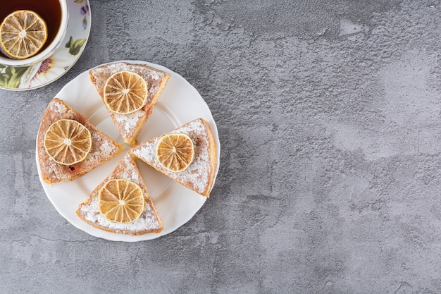 Draufsicht des geschnittenen kuchens mit tasse tee auf grau.
