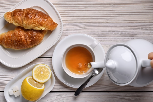 Draufsicht des gießens von tee auf eine tasse mit zitrone und croissants auf weißem tisch