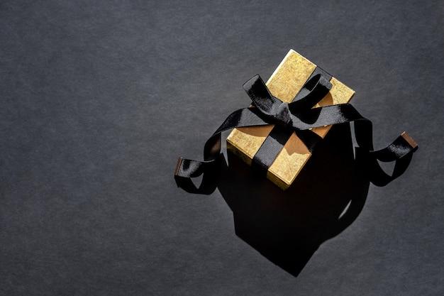 Draufsicht des glänzenden goldenen weihnachtsgeschenks mit schwarzem band auf schwarzem hintergrund