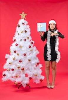 Draufsicht des glücklichen mädchens in einem schwarzen kleid mit weihnachtsmannhut, der nahe weihnachtsbaum steht und neujahrsgeschenk auf rot hält