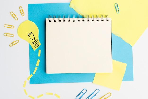 Draufsicht des glühlampeausschnitts und -papierklammer mit leerem gewundenem tagebuch