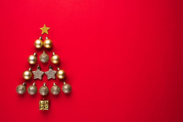 Draufsicht des goldenen balls und des sternes in form des weihnachtsbaums auf rotem hintergrund.