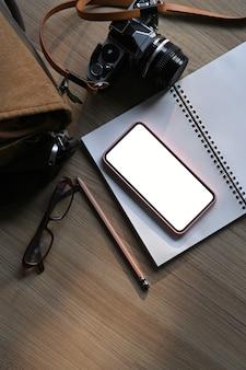 Draufsicht des grafikdesigner- oder fotografenarbeitsbereichs mit kamera, smartphone und notizbuch auf holztisch.