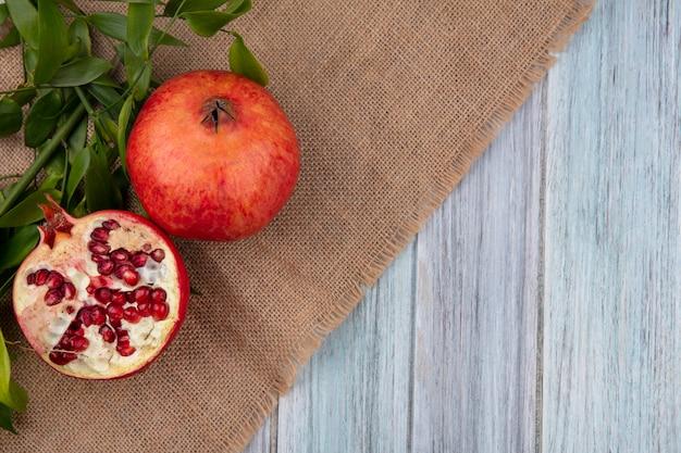 Draufsicht des granatapfels mit blattzweigen auf einer beigen serviette auf einer grauen oberfläche