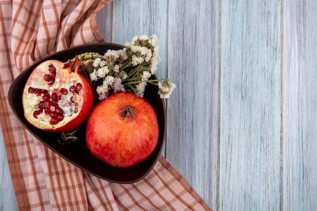 Draufsicht des granatapfels mit blumen in einer schüssel auf einem karierten braunen handtuch auf einer grauen oberfläche