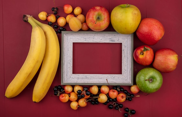 Draufsicht des grauen rahmens mit den pfannkuchen der schwarzen johannisbeeren der bananen und der weißen kirschen auf einer roten oberfläche