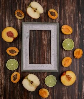 Draufsicht des grauen rahmens mit limettenscheiben pfirsich aprikosen und apfel auf einer holzoberfläche