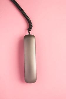 Draufsicht des grauen telefonempfängers auf dem rosa tisch