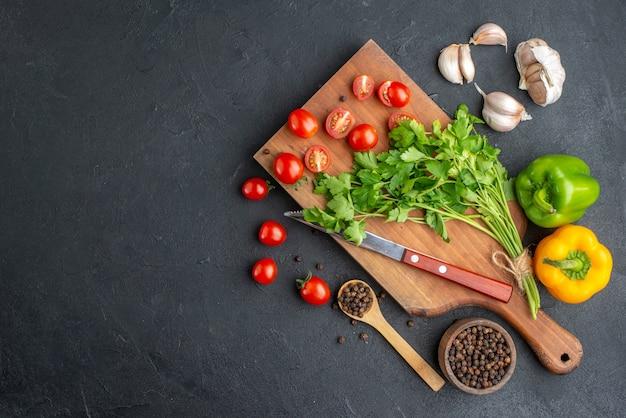 Draufsicht des grünen bündels frischer ganz geschnittener tomaten auf hölzernen schneidebrettmesserpaprika auf der linken seite auf schwarzer notleidender oberfläche