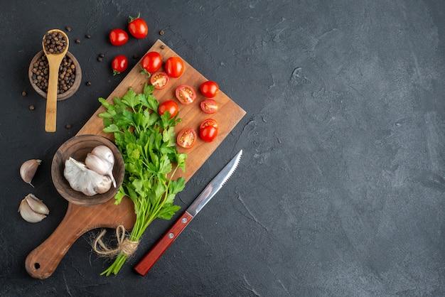 Draufsicht des grünen bündels frischer ganz geschnittener tomaten knoblauch auf holz schneidebrett messer pfeffer auf schwarzer notleidender oberfläche