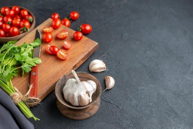 Draufsicht des grünen bündels frischer tomaten auf holzschneidebrett und in schüssel knoblauch auf der rechten seite auf schwarzer notleidender oberfläche