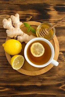 Draufsicht des grünen tees mit zitrone, honig und ingwer im hölzernen schneidebrett