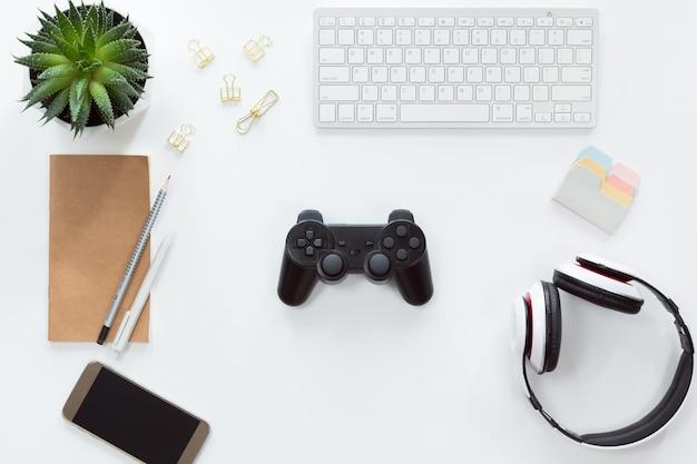 Draufsicht des handys, der computertastatur, des notizbuches, der ebene legen mit steuerknüppel und gamepad, spielkonsole, kopfhörer