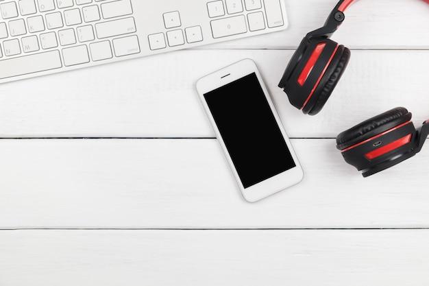Draufsicht des handys mit kopfhörer und tastatur