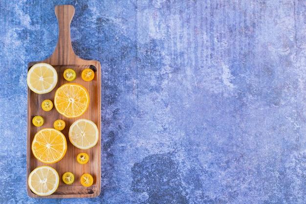 Draufsicht des haufens der frischen zitrusfruchtscheiben auf holztablett.
