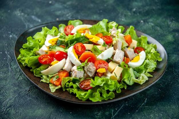 Draufsicht des hausgemachten köstlichen salats mit vielen bestandteilen in einem teller auf schwarzgrünem mischfarbenhintergrund