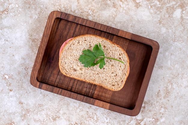 Draufsicht des hausgemachten salamisandwiches auf hölzernem teller.