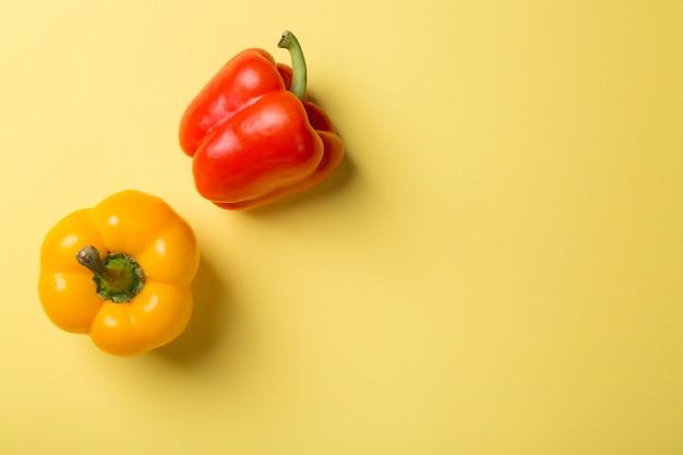 Draufsicht des hellen gelben und roten paprikapaprikas auf gelb
