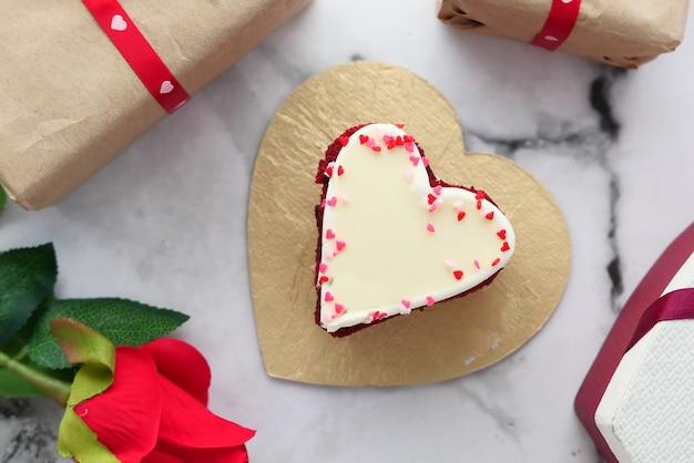 Draufsicht des herzformkuchens, der geschenkbox und der rosenblume auf weißem hintergrund