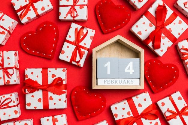 Draufsicht des hölzernen kalenders, der weißen geschenkboxen und der roten textilherzen