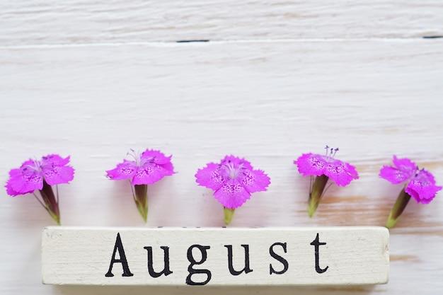 Draufsicht des hölzernen kalenders mit august-zeichen und rosa blumen.