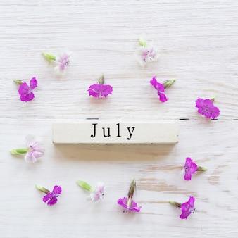 Draufsicht des hölzernen kalenders mit sighn juli und rosa blumen.