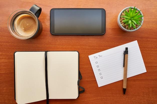 Draufsicht des hölzernen schreibtisches mit einem kaffee, einem mobiltelefon, einem notizbuch und einem stift hauptstudienkonzept, planung und produktivität.