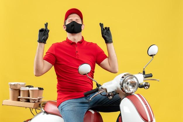 Draufsicht des hoffnungsvollen verträumten jungen erwachsenen, der rote bluse und huthandschuhe in der medizinischen maske trägt, die ordnung liefert, die auf roller auf gelbem hintergrund sitzt