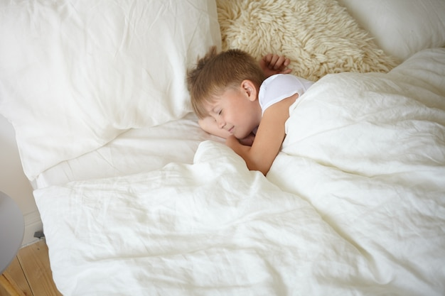 Draufsicht des hübschen entzückenden schülers des europäischen aussehens, der nach dem unterricht in der schule ein nickerchen macht. süßer charmanter junge im weißen t-shirt, der friedlich im bett auf weißen laken schläft und schlafend lächelt