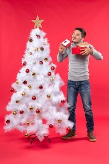 Draufsicht des hübschen erwachsenen in einer grauen bluse, die nahe dem verzierten weißen weihnachtsbaum steht
