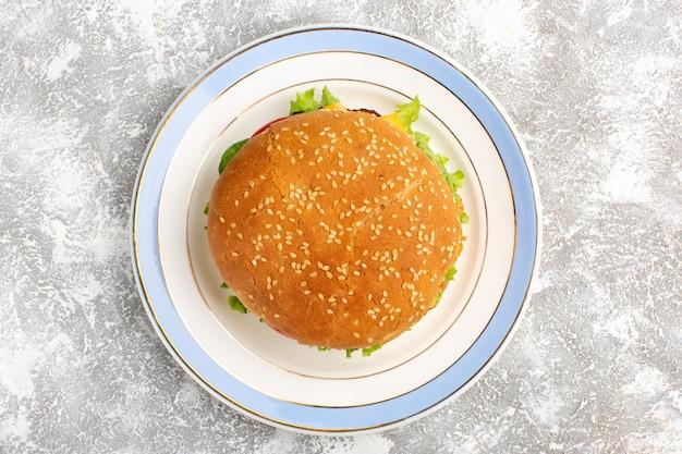 Draufsicht des hühnchensandwiches mit grünem salat und gemüse innen auf weißer oberfläche