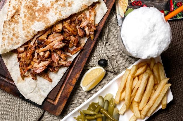 Draufsicht des hühnerkebabs mit fladenbrot serviert mit pommes gurken zitrone und ayran