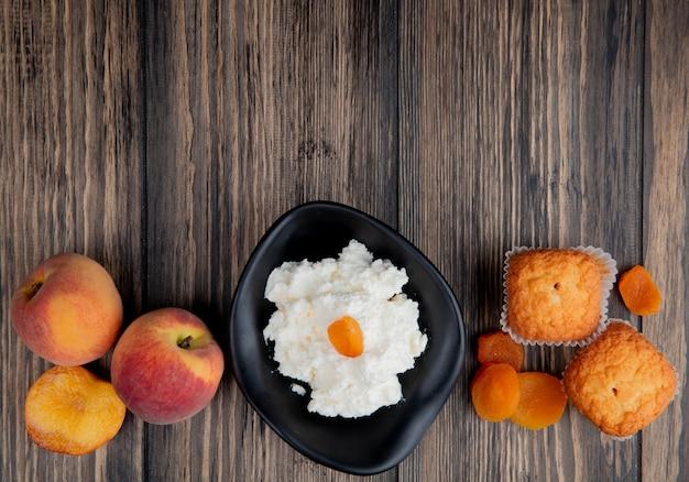 Draufsicht des hüttenkäses in einer schwarzen schüssel mit muffins frischen pfirsichen und getrockneten aprikosen auf rustikalem holz mit kopierraum