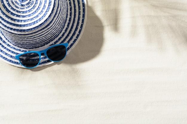 Draufsicht des hutes auf sand mit und blauer sonnenbrille