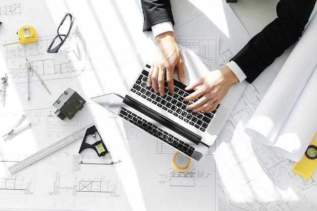 Draufsicht des ingenieurs, der formellen anzug trägt, der am bauprojekt unter verwendung des laptops arbeitet