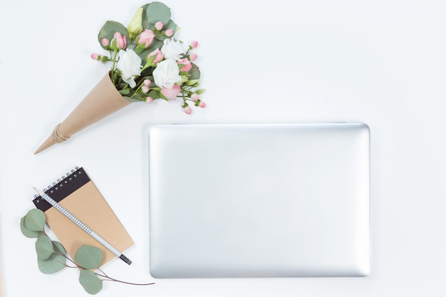 Draufsicht des innenministeriumdesktops des laptops, der blumen auf kegel und des notizbuches. flache lage des arbeitsbereichs mit kopienraum
