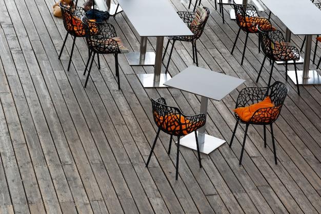 Draufsicht des innenraums des cafés mit durchbrochenen stühlen, hellen kissen und grauen tabellen.